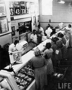 Shoppers at the butcher counter of A grocery store. Garden City, 1942.