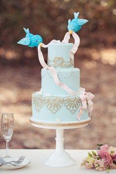 Gâteau de mariage romantique avec des oiseaux bleus survolant le gâteau.