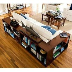 Wrap a floating couch in bookcases instead of tables. would only need the back one since the other sides are too close to walls, etc.