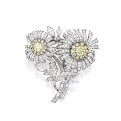 PLATINUM, COLORED DIAMOND AND DIAMOND BROOCH The entwined flowers centered by two round diamonds of yellow hue weighing 2.39 and 1.85 carats, each framed by small round diamonds of yellow hue weighing approximately 1.80 carats, further set with numerous round, baguette and marquise-shaped diamonds weighing approximately 9.35 carats