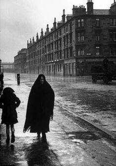 Woman and child walking down street in Glasgow slum.