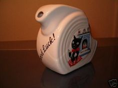 """Fiesta® Dinnerware Good Luck Cat Mini Disc Pitcher features cute black cat sitting by fire and the words 'Good Luck!' on the front. Backstamp on bottom of pitcher says """"China Specialities"""", Exclusive Limited Edition. Made by Homer Laughlin China Company 