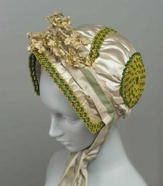 White silk satin profile bonnet with green chenille and yellow cording braid trim, green striped ribbon, and cloth flowers, French, 1805-10.