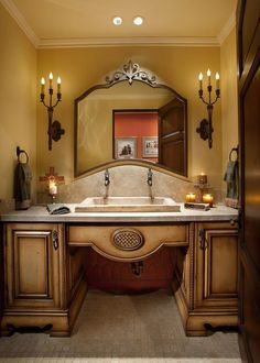 Light fixtures holding a trio of candles flank an ornate, metal mirror in this formal Mediterranean bathroom. A gorgeous stone sink, warm glowing candles, and a wood vanity adds to the elegant, Mediterranean feel. Mediterranean Bathroom, Mediterranean Style, Stone Sink, Metal Mirror, Wood Vanity, Spanish Style, Beautiful Bathrooms, Beautiful Homes, Interior Design