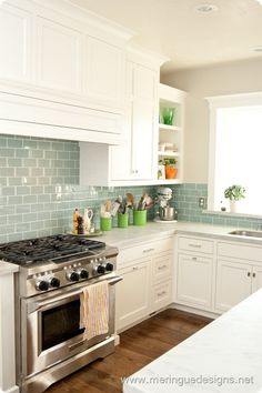 blue green subway tile in white kitchen. I love colored glass subway tile Kitchen Redo, New Kitchen, Kitchen Remodel, Kitchen Cabinets, Kitchen White, Kitchen Country, Kitchen Countertops, Aqua Kitchen, Open Cabinets