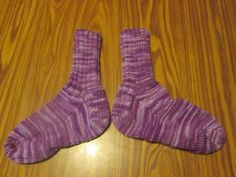 Here is a wonderful pair of hand knit adult size socks. Heel to toe is approx. 9 in. and the ribbing on the top (top to ankle) is approx. 6 1/2 in. The yarn color is called Purple Tones. These socks are made of 100% acrylic yarn and can be machine washed and dried.