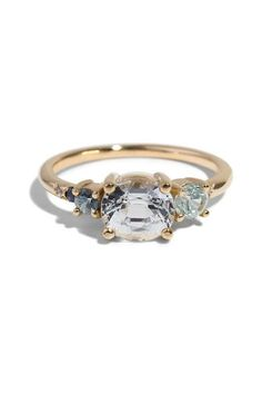 This custom heirloom sapphire shoulder shank ring features a 3mm zircon, a 3mm white sapphire trillion, a 2.5mm seafoam sapphire, and a bead set 1.3 seafoam sapphire set in a shoulder shank which tapers from 2mm to 1.5mm, finished in 14kt yellow gold.