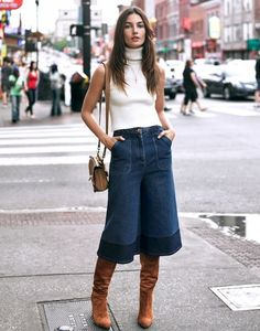 Lily Aldirdge wears high-neck knit tank top is paired with denim culottes, knee-high suede boots, and a neutral shoulder bag.