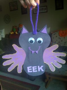 Construction paper bat with purple handprints on cardboard. Googly eyes makes everything adorable, purple painted smile and foam fangs. Pipe cleaner hanger. Sweet! Halloween craft, Halloween crafts for kids, preschool, kids craft