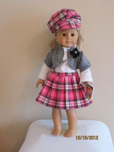 American Girl Doll is wearing a pleated skirt, short jacket over white knit top and is set off with hat