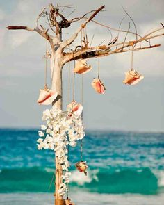 """In order to achieve a natural-looking aesthetic that wouldn't detract from the beauty of the beach, branches, shells, and small orchids were used to create """"driftwood"""" ceremony decorations."""
