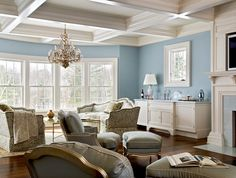 A coffered ceiling can also be used to counterbalance a room's decor. Here, this elegant and all-white, deeply coffered ceiling adds structure and visual weight to the room, balancing the wall color and furniture style.
