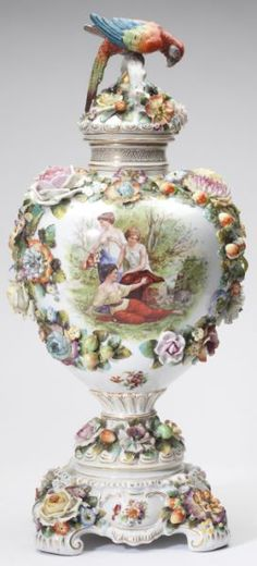 Royal Vienna Porcelain Covered Urn, 19th Century, impressive form heavily encrusted with flowers and fruit, the colorful and life like parrot finial sits atop a branch-form handle, above a baluster vase painted with a scene of young Beauties relaxing  by a Stream, the verso with floral clusters, raised on a plinth having 4 cyma scrolled feet