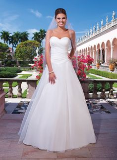 Sweetheart Gowns sweetheart style 6042 Asymmetric pleated organza bodice with a sweetheart neckline and a  basque waist on an A-line organza skirt. The back is finished with  organza covered buttons to the bottom of the basque waist and a chapel  length train.