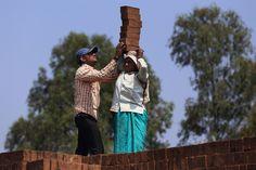 Trabalhadores na preparação de tijolos em um forno. Uma transportadora feminina, ajudada por um homem, coloca no chão os tijolos de sua cabeça em uma área de forno na fábrica tradicional de tijolos na vila Bhosalewadi, perto da cidade de Karad, estado de Maharashtra, Índia. Um transportador, geralmente meninas ou mulheres, podem equilibrar 10 ou mais tijolos na cabeça.  Fotografia: Sayid Budhi (DocBudie) no Flickr.