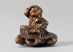 A Tokyo school wood netsuke of Urashima Tarô, by Masayuki. Mid 19th century     With a box, his farewell gift, under his arm, riding on a minogame that is bringing him home after his sojourn at Ryûjin's palace. On his robe a pattern of pine needles, the pine being a symbol of long life. Signed Masayuki with kaô in a gourd-shaped reserve.   Height 3.5 cm