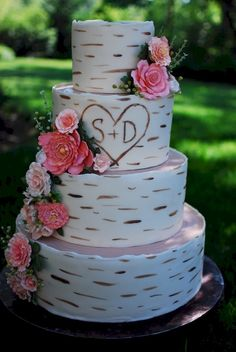 I made this cake recently for a couple getting married.  They brought me 3 different wood-type cakes and we took elements from each to create the design.  The cake is wrapped in Fondarific with hand-painted wood grain and carved initials.