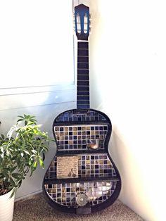 Stunning repurposed guitar shelf with mosaic glass tile backsplash in cobalt blues, black, copper, and amber.