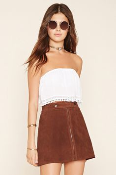This genuine suede mini skirt features an exposed zip front with a snap-buttoned strap accent along the waist.