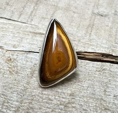 This tiger eye ring pulls you in with its iridescent layers of browns and blacks. The layers mimic the unique organic triangle shape of the stone. It has been set in a sterling silver platform. This t