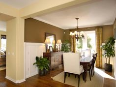 A small, formal dining room combines elegant gold and brown tones. The table and sideboard have massive carved legs. Wainscoting is unusually tall but allows the sideboard to stand out from the wall.