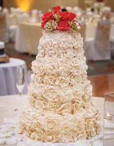 Buttercream tiered wedding cake with rosette design and red flower topper. View more from this regal red Nashville wedding with gold details at Doubletree Downtown Nashville! Cake by Signature Cakes by Vicki. Pic by @robmouldphoto   The Pink Bride www.thepinkbride.com #nashvillewedding