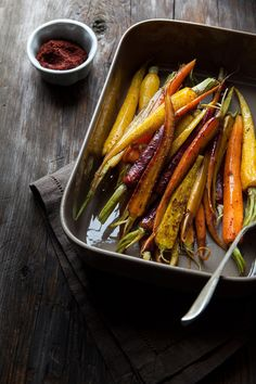 Whole roasted carrots in a metal baking pan