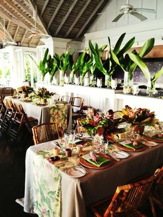 Tropical Wedding By Matthew Robbins Design: Bamboo chairs add a touch of texture and warmth with rattan chargers on tables. A wall of Heliconia leaves on the bar create a lush green backdrop.