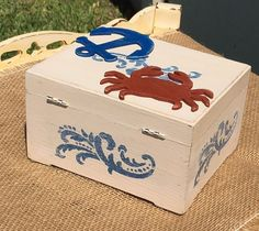 Hand painted and decorated rustic wooden box. Ocean/ sea/ beach/ shore theme with a crab and anchor. Store notes from beach house or event guests photos, and mementos. 5x6 inches  **Not exactly what you want? We accept customer orders! Just send us a message with an idea of what you are looking for and we will let you know what we can do.**  Other Boxes: https://www.etsy.com/shop/OffbeatOccasion?ref=hdr_shop_menu&section_id=20134987