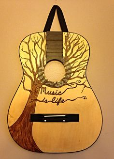 "From trash to treasure~ this guitar wall hanging reuses a guitar front from a broken guitar to depict ""Music is Life"".  A great gift for music lovers!"