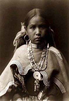 Image of a Jicarilla Maiden.  It was taken in 1905 by Edward S. Curtis.The image shows the Indian Maiden in a half-length portrait, facing right. It is a nice illustration showing traditional Indian dress.
