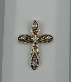 Vintage 10K cross pendant set with six round brilliant diamonds. Gentle loops form the cross with sublet diamond accents. A classic design from the 1970s. Sure to be appreciated by the wearer for the fine craftsmanship which allows light through the piece.  Details: Solid 10K Yellow Gold: (shown in picture)  Natural Diamond: (5) 1.0 mm round Approximate Stone Weight: 0.03 ct. Diamond Clarity: I1 Diamond Color: G  Pendant Dimensions: 20 mm x 27 mm  Shipping by USPS Priority Mail Signature…