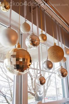 Christmas balls on ribbon hanging from curtain rod - various heights and sizes but consistent color scheme - Cuckoo 4 Design