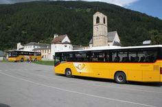 Swiss yellow postal buses stop in front of Kloster St Johan in Müstair in Graubünden in the far southeastern corner of Switzerland. An hourly bus goes to the Engadin Valley via the Offenpass with further services available during the summer season. Post Bus, Carolingian, Bus Stop, St John's, Buses, Switzerland, Poster, Yellow, Summer