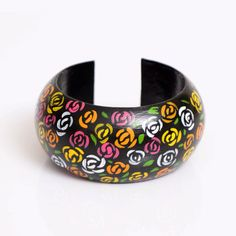 Wooden bracelet, hand painted by artisans from Ayacucho.  For each product you buy, KANI will give a headwear for sun protection for children.    Measures:    3.8cm width   6.6-6.8cm  diameter