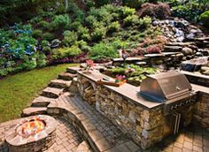 Rather than fight the sloping property, YardApes used it to create a picturesque waterfall that flows into a koi pond. A stone-veneer retaining wall provides two sides of the pond and is the base for a built-in grill. A masonry fire pit anchors an all-season seating area, which looks out over a patch of lawn and resilient mix of border plants, including spirea shrubs, endless summer hydrangea, and ornamental grasses.