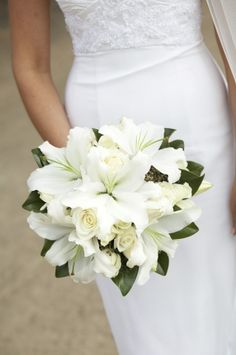 All white bouquet with lilies and a navy blue ribbon. :)                                                                                                                                                                                 More