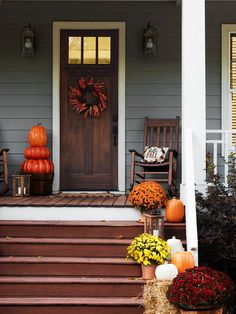 Bathe your home in autumn splendor. This outdoor decor adds maximum eye appeal for minimal cost. #lowes #mums #pumpkins #frontdoor #wreath