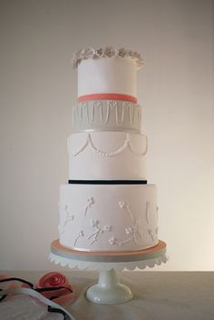 Dylan Wedding Cake by Charm City Cakes - Beautiful white on white tiered cake with peach, blue, and grey accents.