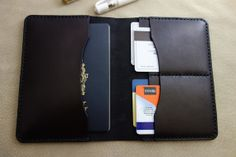 Leather Passport Cover / Wallet: Black leather and stitching. Holds 2 passports (left side), 4 card holder slots,
