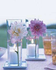Flowers and candlelight are nothing new, but together they create tabletop decorations fit for relaxed summer entertaining. Place votive candles in tall glass vessels, and attach a flower (dahlias are shown here) outside each, trimming the stem to fit and tying with raffia that matches the flower. Set each display in a saucer of water to keep the flowers fresh.