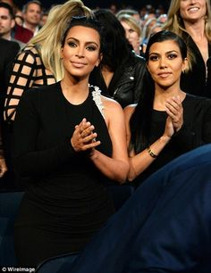 Beaming with pride! Kim looked poised as she applauded Caitlyn beside sister Kourtney...