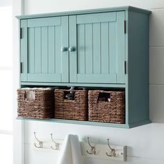 Storage doesn't have to be stark. Our handsome wood cabinet features three hand-woven banana leaf baskets and upper wainscot-detailed doors. Sized to fit perfectly above your toilet and hide all your powder room essentials.