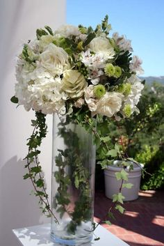 ivy centerpiece + like the glass and ivy showing - hate the roses in this Elegant Centerpieces, Wedding Centerpieces, Cylinder Centerpieces, Tall Centerpiece, Wedding Arrangements, Floral Arrangements, Vase Haut, Ivory Roses, Wedding Flowers