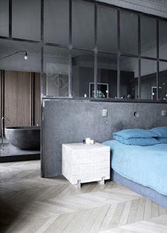 Une verrière qui fait office de mur et de tête de lit pour une belle suite parentale entre la chambre et la salle de bains.