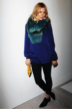 Sienna Miller dresses up a casual sweater and skinny pants with an aqua fur collar and yellow clutch