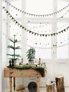 もみの木などを置いたディスプレイ台の上に、様々な柄のガーランドを飾って。白と緑がテーマカラーの空間。植物の写真や画像の紙をカットしたガーランドもあり、白が基調の空間によく映えています。
