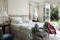 French doors add an element of indoor/outdoor living to Cynthia Frank's master bedroom. Based around a neutral color palette, floral accents and upholstered chairs add pops of color to the space.