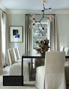 The dining room is an exercise in restraint. Everything, except or the artwork is completely neutral. The slipcovered chairs and dining table have clean, minimal lines,  while the Lindsay Adelman chandelier .  The 1920s Dutch Colonial house had undergone multiple renovations over the years, but the current owners, along with interior designer, Kristin Rowell of Scavullo Design and architect Carl Hesse of Three Design Studios