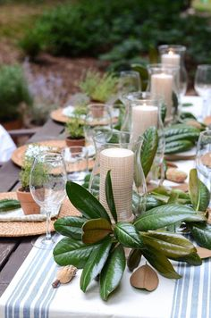 Friendsgiving or Thanksgiving table setting ideas. Earthy candles, potted herbs, and magnolia leaves decorate this festive table. Table Arrangements, Flower Arrangements, Magnolia Leaves, Magnolia Table, Wedding Decorations, Table Decorations, Wedding Centerpieces, Outdoor Table Centerpieces, Outdoor Table Decor